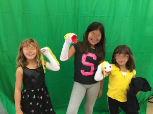 Students getting a picture with their sock puppets in front of the green screen